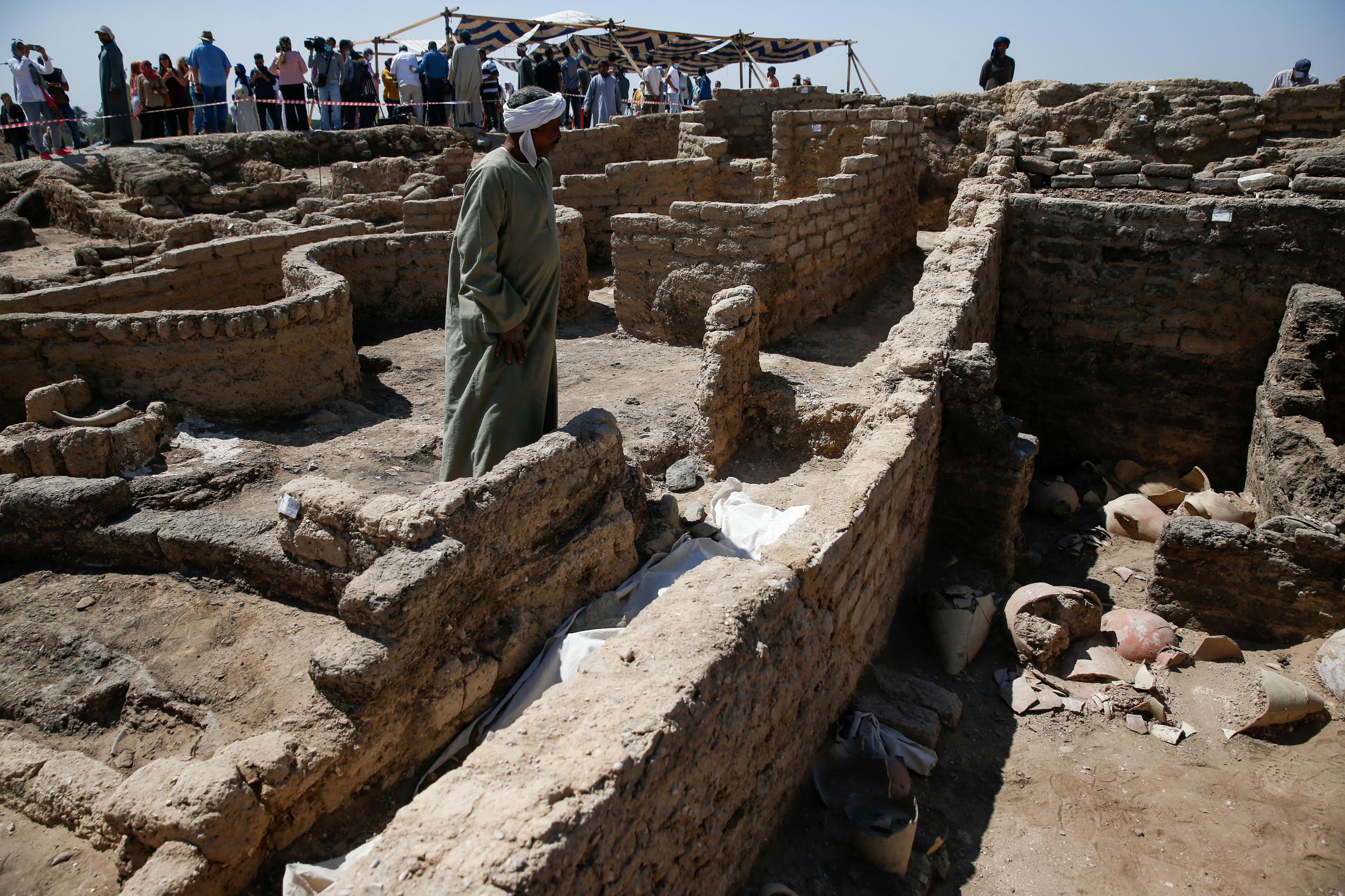Un hombre de pie muestra alguno de los hallazgos que forman parte de la ciudad descubierta cerca de Luxor, de más de 3.000 años de edad. REUTERS/Amr Abdallah Dalsh