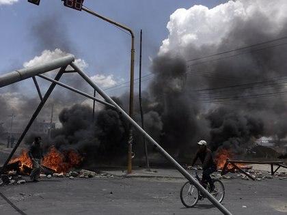 Un ciclista pasa junto a una planta de gasolina bloqueada de Senkata en las afueras de El Alto, La Paz, Bolivia, el 19 de noviembre de 2019 (REUTERS/David Mercado)