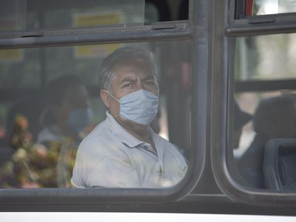 A man wears a face mask at a public bus as a preventive measure against the spread of the new coronavirus, COVID-19, in Mexico City, on March 26, 2020. (Photo by PEDRO PARDO / AFP)
