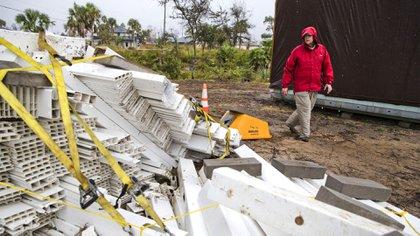 Chris Anderson ata los materiales de construcción y otros objetos de su césped a medida que se acerca la tormenta tropical Néstor, el viernes 18 de octubre de 2019 en México Beach, Florida (Joshua Boucher/News Herald via AP)