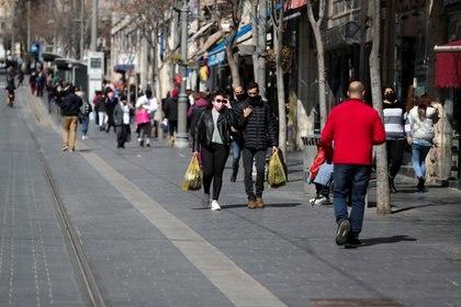 Des gens portent des sacs à provisions à Jérusalem le 21 février 2021. REUTERS / Ammar Awad