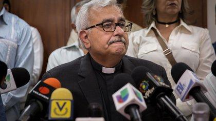 El sacerdote José Virtuoso (c) habla con la prensa durante la jornada de elecciones presidenciales en Caracas (Venezuela).
