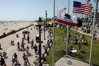 Varias personas pasean en bicicleta mientras otras permanecen sentadas en la hierba en Huntington Beach durante el Día de los Caídos, en California, Estados Unidos, el 23 de mayo de 2020. REUTERS/Patrick T. Fallon