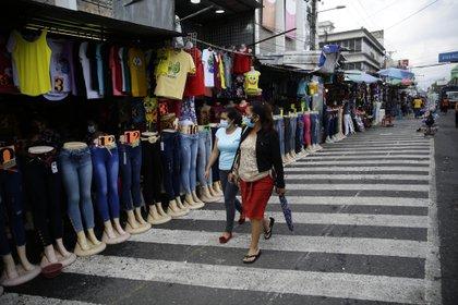 Dos mujeres caminan frente a ventas de ropa en el centro de San Salvador. EFE/Rodrigo Sura/Archivo