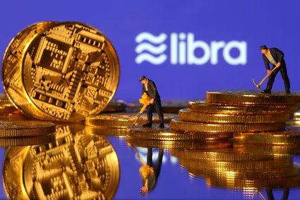 FILE PHOTO: Small toy figures are seen on representations of virtual currency in front of the Libra logo in this illustration picture, June 21, 2019. REUTERS/Dado Ruvic/File Photo