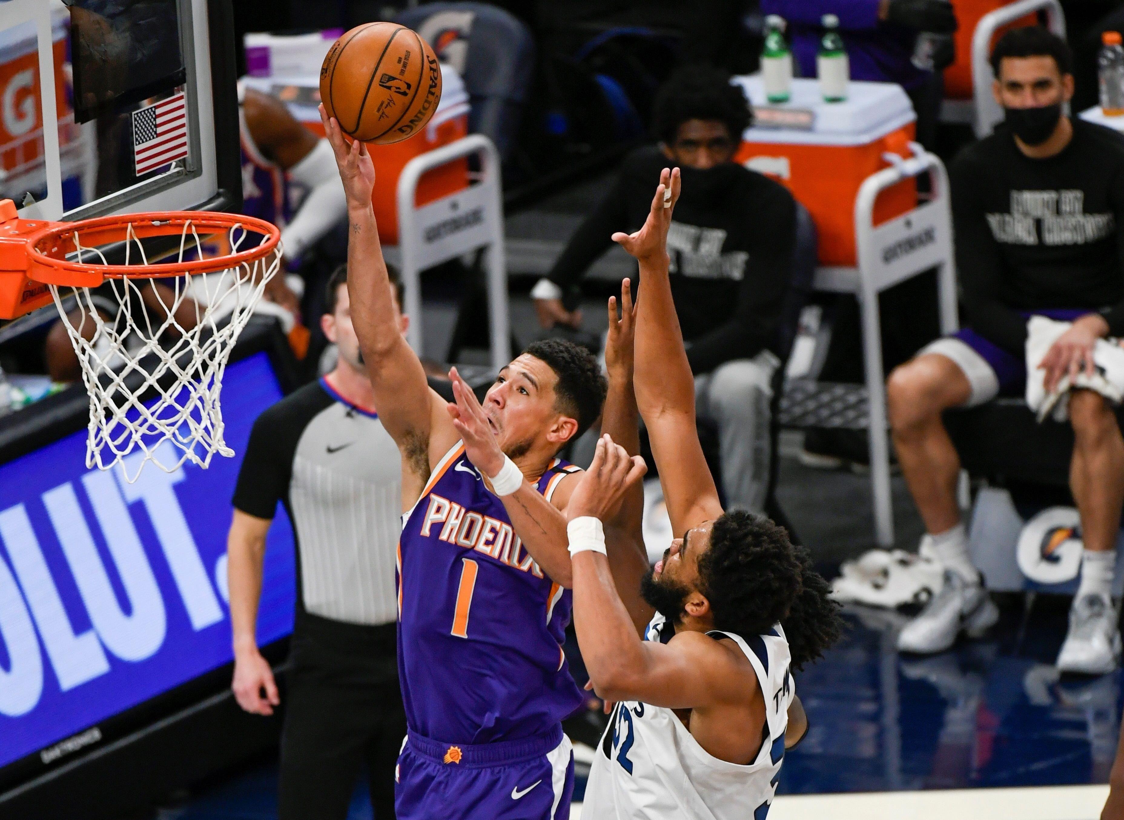 Devin Booker (c), escolta hispano de los Suns de Phoenix, fue registrado este domingo al atacar el aro que defiende Karl Anthony Towns (d), de los Timberwolves de Minnesota, durante un partido de la NBA, en el Target Center stadium de Minneapolis (Minnesota, EE.UU.). EFE/Craig Lassig