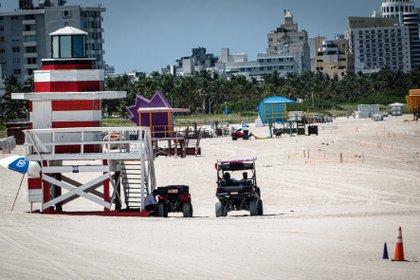 Unos trabajadores recogen sillas y parasoles este viernes en la playa de Miami Beach, Florida. EFE/Giorgio Viera