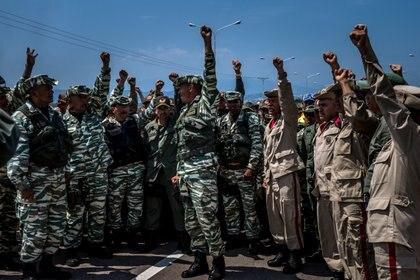 Soldados venezolanos y miembros de la milicia alzan sus puños cerca del puente que conecta Venezuela y Colombia para que los medios del Estado graben mientras demuestran su apoyo al presidente Nicolás Maduro. (Meridith Kohut para The New York Times)