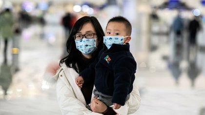 Una mujer y un niño usan barbijos en el aeropuerto internacional de Daxing en Beijing (Photo by NICOLAS ASFOURI / AFP)