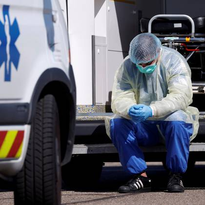 A health worker wearing a protective gear takes a break during transfer operations of patients infected with coronavirus disease (COVID-19) from Strasbourg to Germany and Switzerland, France March 30, 2020. REUTERS/Christian Hartmann     TPX IMAGES OF THE DAY