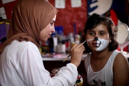 La artista palestina Raneen Alzerie pinta una máscara de un personaje de dibujos animados en el rostro de una niña en el sur de la Franja de Gaza el 21 de septiembre de 2020 (REUTERS/Ibraheem Abu Mustafa)