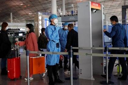 Personal sanitario revisa a los pasajeros que ingresan al aeropuerto Capital de Beijing (Reuters)