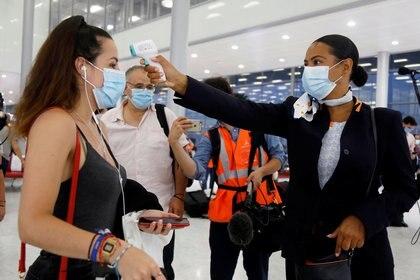 Una persona del staff del aeropuerto le toma la temperatura a una pasajera usando un tapabocas