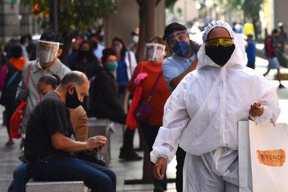 Un transeúnte viste un traje de alta seguridad sanitaria durante sus compras en el Centro histórico de Ciudad de México (Foto: EFE)