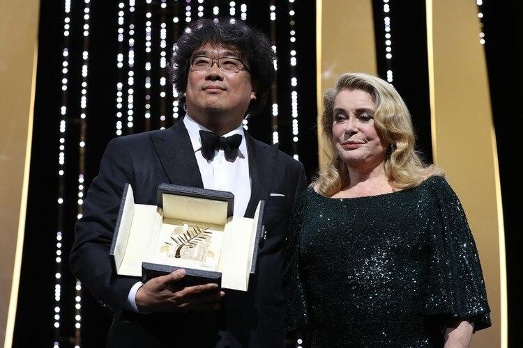 """Bong Joon-Ho junto a Catherine Deneuve al recibir la Palma de Oro por """"Parasite"""" en Cannes (Photo by Valery HACHE / AFP)"""