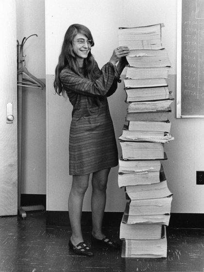 Hamiton junto a los códigos de programación que se usaron en el software de la computadora AGC que se utilizó en la misión Apolo 11.