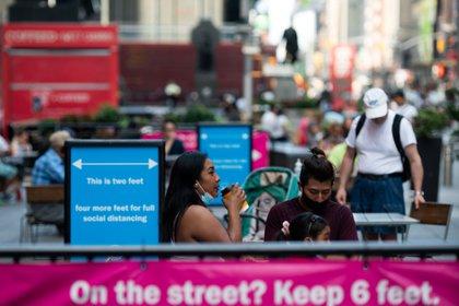 Una mujer con una máscara protectora bebe una taza de café mientras está sentada en una mesa al aire libre en Times Square