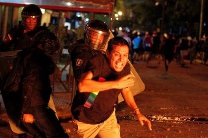 Policías persiguen a los manifestantes en Paraguay (César Olmedo/Reuters)