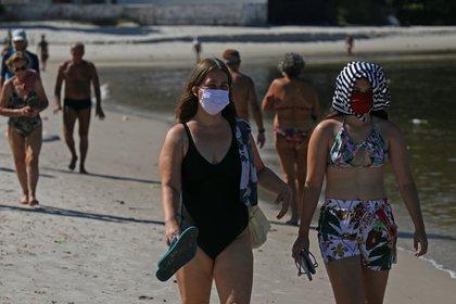 Una grupo de personas camina por una playa en la ciudad de Niterói, vecina de Río de Janeiro. EFE/Fabio Motta/Archivo