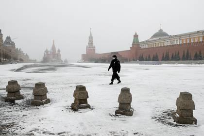 Un policia custodia con una marcarilla una Plaza Roja de Moscú desierta.
