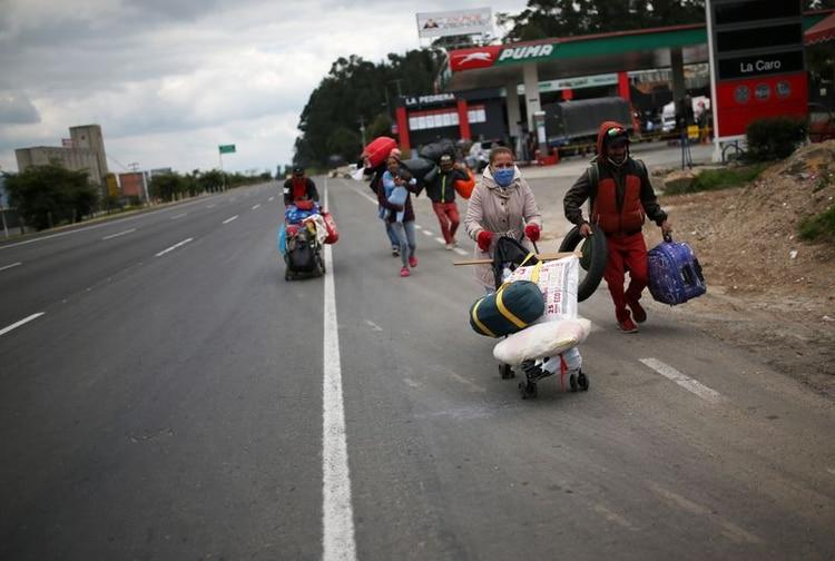 Migrantes venezolanos caminan de regreso a su país desterrados por los efectos del coronavirus cerca a la ciudad de Chía, Colombia (REUTERS/Luisa González)