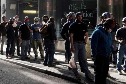 FOTO DE ARCHIVO: Trabajadores de la construcción esperan en la fila para hacer una prueba de temperatura para volver al lugar de trabajo después del almuerzo, en el barrio de Manhattan de la ciudad de Nueva York, Nueva York, Estados Unidos, 10 de noviembre de 2020. REUTERS/Carlo Allegri