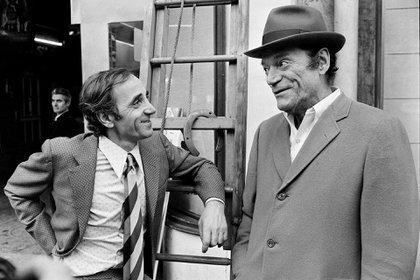 Charles Aznavour y Eddie Constantine conversan en una calle de París en noviembre de 1972 (AFP)