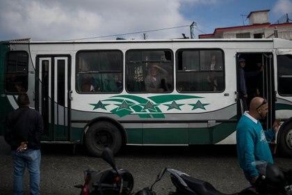 Pasajeros de un autobús observan hacia el lugar donde se realiza una operación contra el grupo liderado por el policía Óscar Pérez