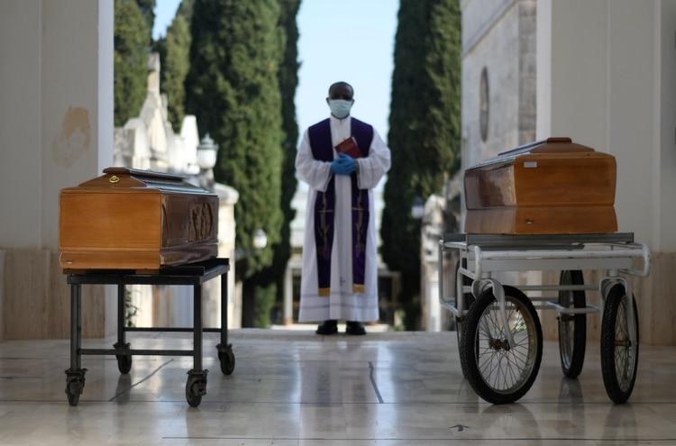 Los ataúdes de dos víctimas de coronavirus, en un entierro en Cisternino, Italia (Reuters)