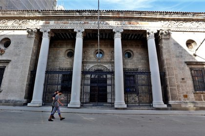Dos personas caminan frente a una sede de un banco cerrado en La Habana
