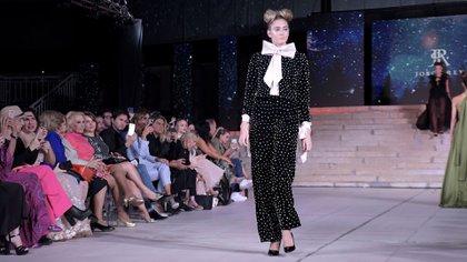 Como novedad del desfile y llamativo para todos los presentes, un conjunto de pantalón oxford y buzo en chiffón negro con perlas y maxi moño rosa