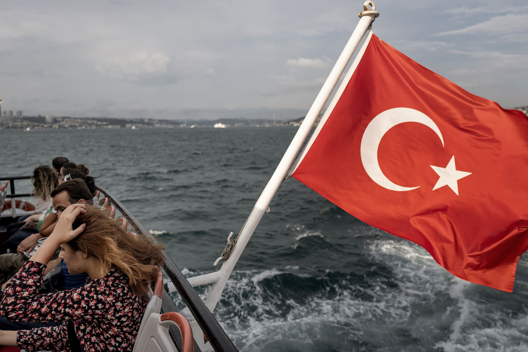 City commuters cross the Bosporus Strait on a passenger ferry flying Turkey's national flag from its stern in Istanbul, Turkey, on Friday, Aug. 17, 2018. Turkish President Recep Tayyip Erdogan argued citizens should buy gold, then he said sell. Add dramatic swings in the lira, and the country's traders are now enthusiastically doing both. Photographer: Ismail Ferdous/Bloomberg