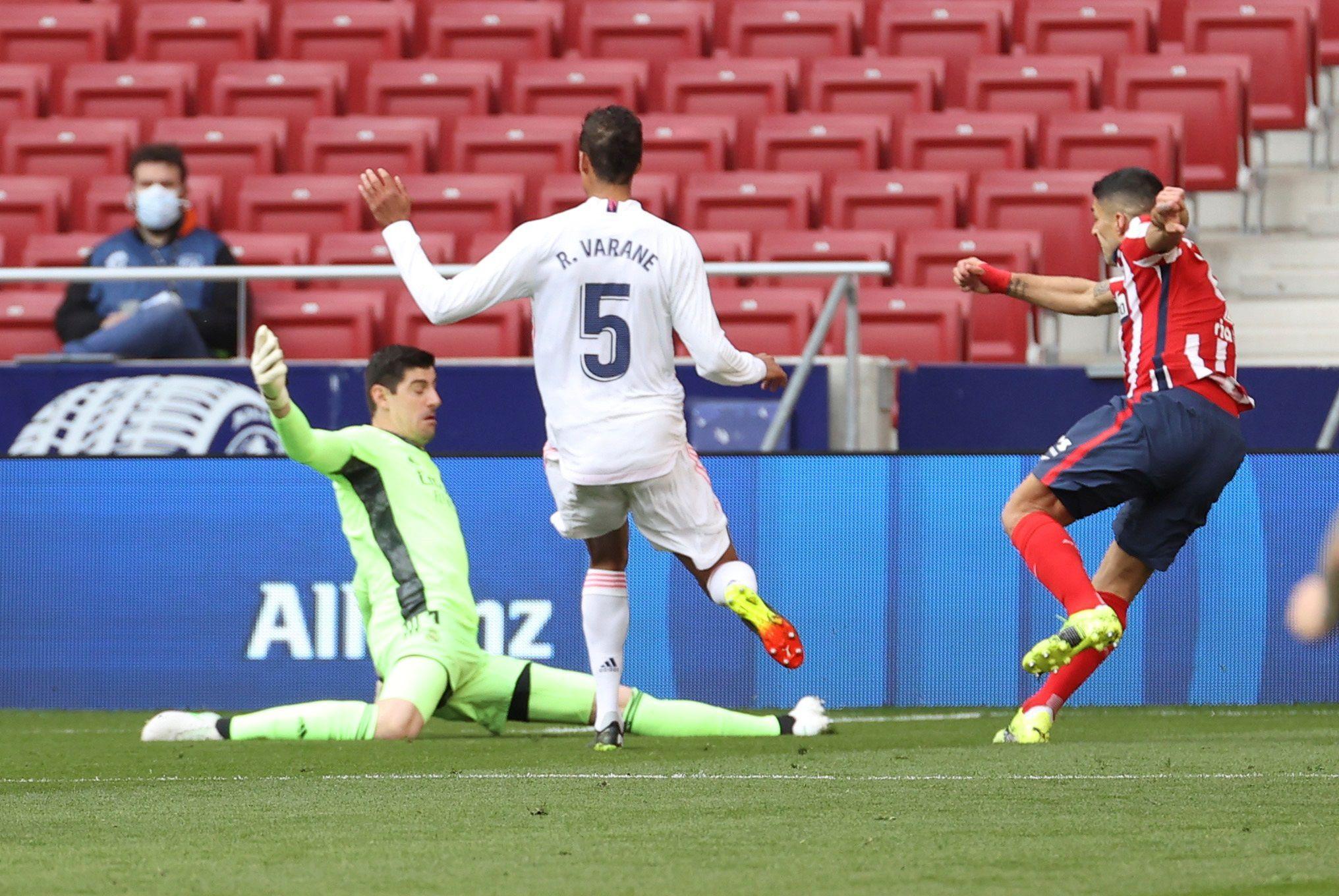 El delantero uruguayo del Atlético de Madrid Luis Suárez (dcha) remata para conseguir el primer gol ante el portero belga del Real Madrid, Thibaut Courtois, durante el partido de Liga que disputaron en el estadio Wanda Metropolitano de Madrid.EFE/JuanJo Martín