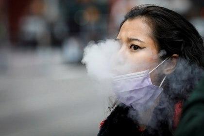Una mujer fuma un cigarrillo electrónico en Times Square, durante la pandemia de coronavirus (REUTERS/Brendan McDermid)