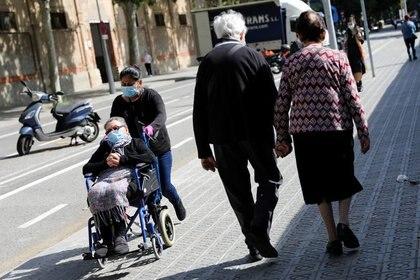 Una pareja camina mientras una mujer es empujada en una silla de ruedas durante las horas en que se permite a los ancianos caminar al aire libre, por primera vez desde que se anunció el cierre, en medio del brote de la enfermedad coronavirus (COVID-19), en Barcelona, España, el 2 de mayo de 2020. REUTERS/Nacho Doce