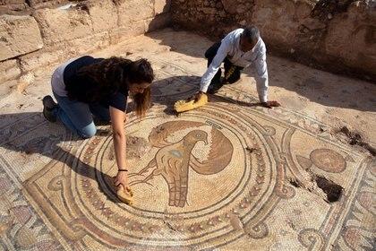 """Dos trabajadores de la Autoridad de Antigüedades de Israel limpian el piso de mosaico donde se puede ver la """"Águila Imperial"""", un símbolo típico de la cultura bizantina. (REUTERS / Ronen Zvulun)"""