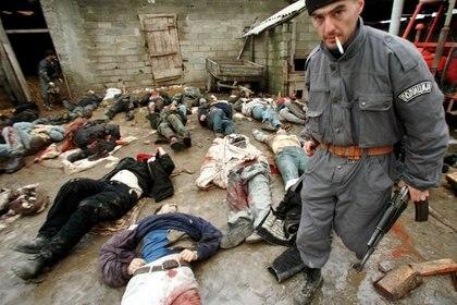 Un policía serbio le quita el rifle de asalto al cadáver de un supuesto miembro de la guerrilla de Kosovo en enero de 1999. (REUTERS/Yannis Behrakis)