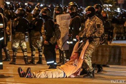 Un policía arrastra a un hombre durante los enfrentamientos entre las fuerzas de seguridad y los manifestantes tras las elecciones presidenciales en Minsk (Dmitry Brushko/Tut.By via REUTERS)