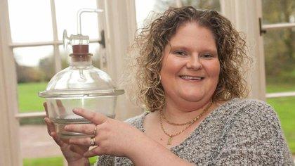 """Louise Brown sostiene el contenedor donde fue incubado su embrión después que el óvulo de la madre se fertilizara con el esperma del padre en un """"Petri Dish"""", o platillo de Petri."""