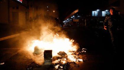 Un efectivo militar corre al lado de una fogata realizada por los manifestantes este viernes, durante una manifestación en Asunción (EFE/Nathalia Aguilar)