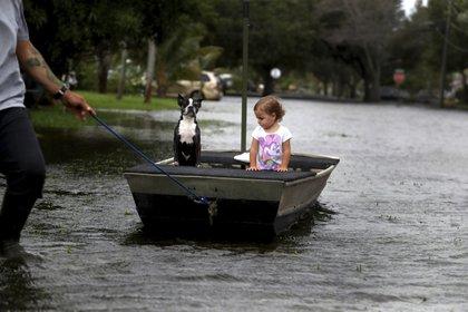 Lemay Acosta tira de un bote con su hija, Layla, de dos años, y su perro, Buster, dando un paseo en su barrio inundado en Plantation, Florida, el lunes 9 de noviembre de 2020, al día siguiente de que la tormenta tropical Eta tocara tierra en los Cayos de Florida e inundara partes del sur de Florida. (Carline Jean/South Florida Sun-Sentinel via AP)