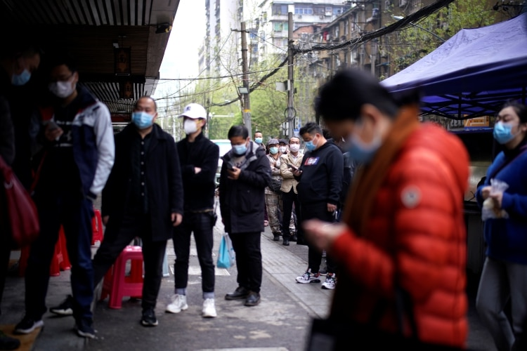 Personas con barbijo en Wuhan, la ciudad china donde se cree que comenzó el brote (REUTERS/Aly Song)