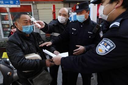 FOTO DE ARCHIVO. Un funcionario mide la temperatura un hombre mientras la policía inspecciona sus documentos, en Wuhan, provincia de Hubei, China. 20 de febrero de 2020. Imagen proporcionada por un tercero. China Daily vía REUTERS.