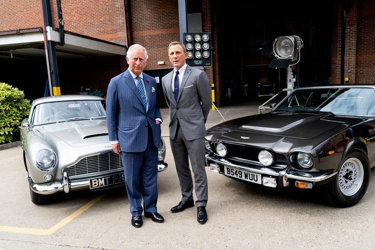 """El Príncipe Carlos con Daniel Craig y los Aston Martin DB5 y V8 Vantage que también participan de """"No time to die"""""""