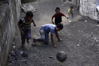 Niños juegan en una calle cubierta de cenizas en Patrocinio (Orlando  ESTRADA / AFP)