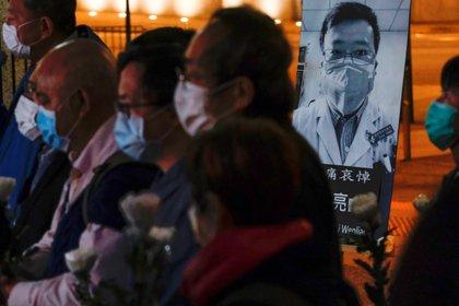 Personas con máscaras asisten a una vigilia por el difunto Li Wenliang en Hong Kong, el 7 de febrero de 2020 (REUTERS/Tyrone Siu)