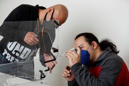Fotografía del 15 de mayo de 2020 del escultor y artista visual, Ricardo Atl (d), trabajando en el diseño de una caja de aerosol para que los doctores mexicanos se protejan de COVID-19, en Ciudad de México (México). EFE/José Méndez