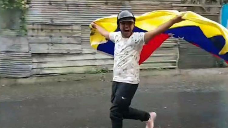 Fotograma del video que se hizo viral de Jhonny José Godoy Buitrago corriendo con una bandera venezolana mientrasgrita contra Nicolás Maduro el 23 de enero de 2019