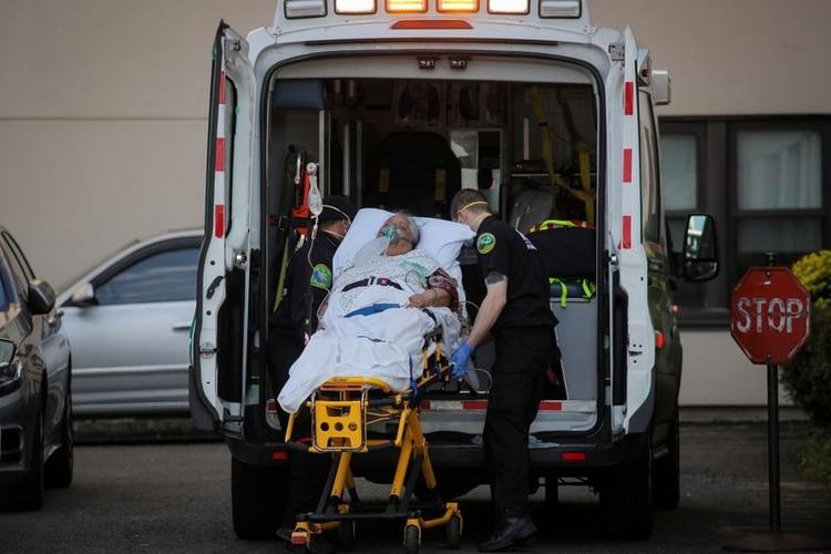 Una mujer es llevada a una ambulancia por los paramédicos en un centro de salud en Brooklyn durante el brote de coronavirus (COVID-19) en Nueva York [14 de abril de 2020] (Reuters/ Brendan McDermid)