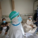 A medical worker in protective suit inspects a CT scan image at a ward of Wuhan Red Cross Hospital in Wuhan, the epicentre of the novel coronavirus outbreak, in Hubei province, China February 24, 2020. Picture taken February 24, 2020. China Daily via REUTERS ATTENTION EDITORS - THIS IMAGE WAS PROVIDED BY A THIRD PARTY. CHINA OUT.